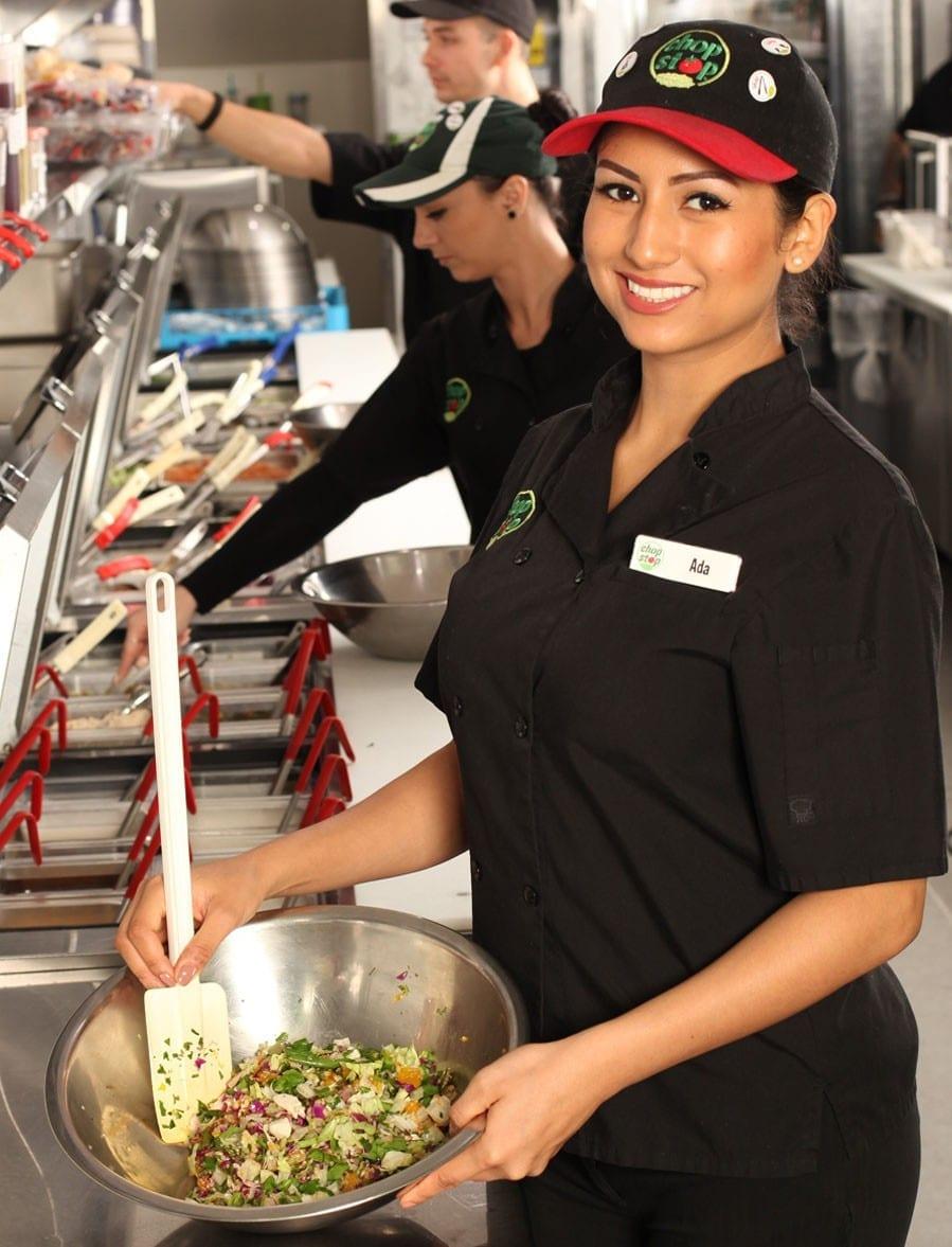 chopstop employee mixing chopped salad